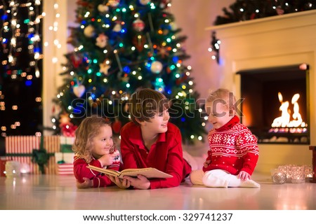 Children read a book and open gifts at fireplace on Christmas eve. Family with child celebrating Xmas. Decorated living room with tree, fire place, candles. Winter evening at home for parents and kids - stock photo