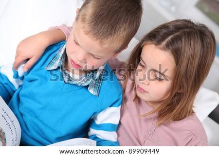 Children reading book at home - stock photo