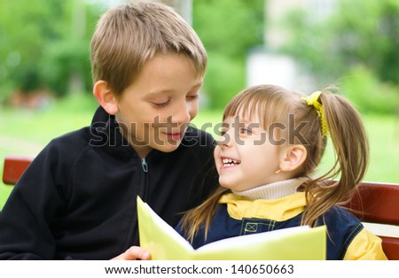 children reading the book at the park - stock photo
