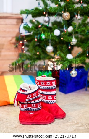 Children red boots standing next to the Christmas tree with gifts - stock photo
