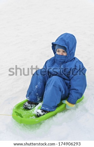 Children ridding on a sled in winter season - stock photo