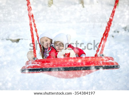 children ride on a swing in winter park - stock photo