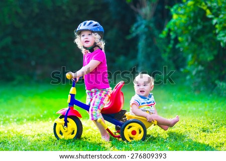 Children riding a bike. Kids enjoying a bicycle ride. Little preschooler girl and baby boy, brother and sister, having fun outdoors. Active toddlers play in the garden. - stock photo