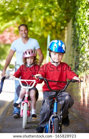 Children Riding Bikes On Their Way To School With Father - stock photo