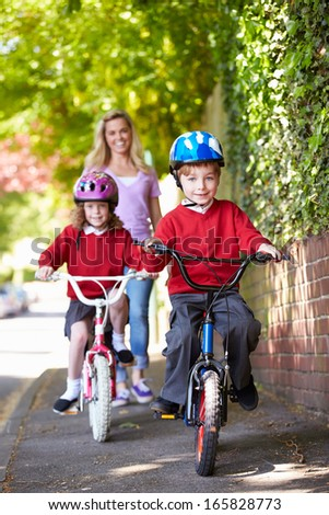 Children Riding Bikes On Their Way To School With Mother - stock photo