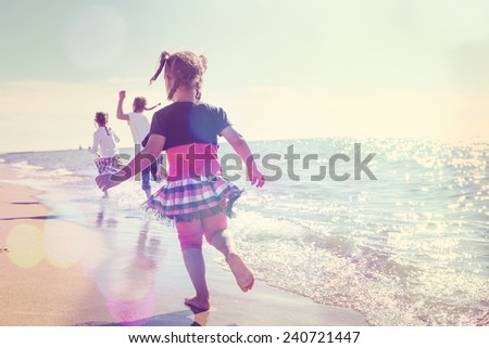Children running on the beach in the waves - stock photo