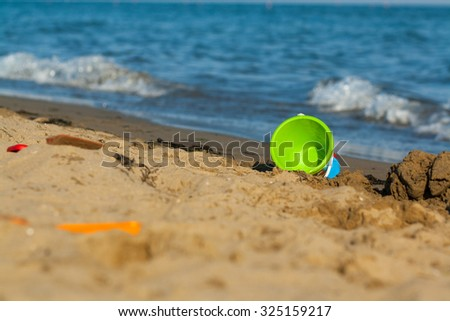 Children's beach toys - buckets, spade and shovel on sand on a sunny day. Sea as background. Wet sand and waves. Different colors of toys. - stock photo