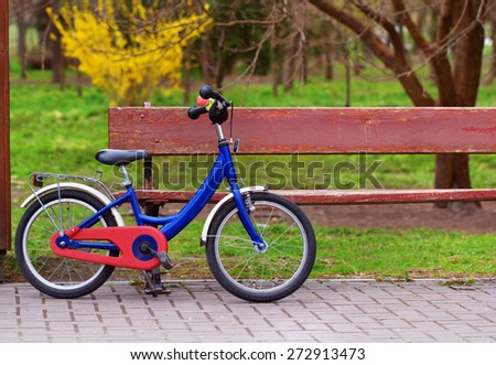 Children's bicycle parked by the bench in the park - stock photo
