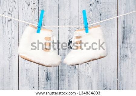 Children's boots hanging on a clothesline. - stock photo