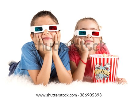 Children's couple with 3d glasses and popcorn - stock photo