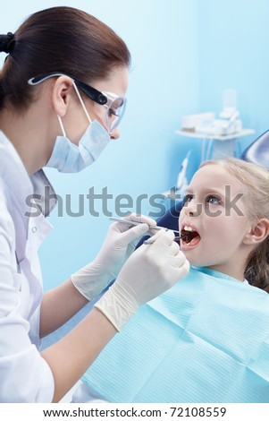 Children's doctor treats your child's teeth - stock photo