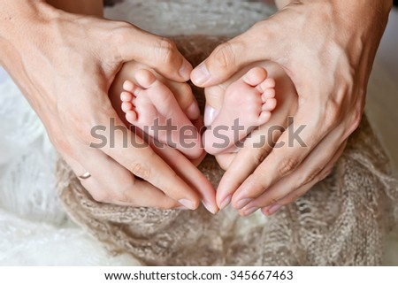 Children's feet in hands of mother and father.  Mother, father and Child. Happy Family concept. Beautiful conceptual image of Motherhood - stock photo