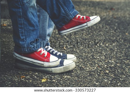 Children's feet in sneakers on the background of adults. Father and child sitting on a bench. - stock photo