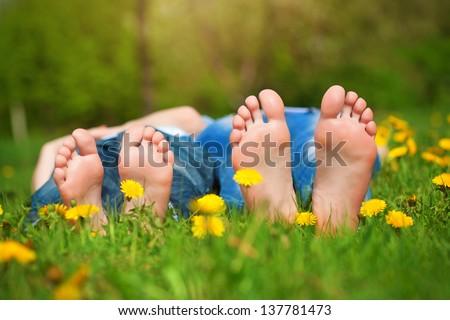 Children's feet  on grass. Family picnic in  park - stock photo
