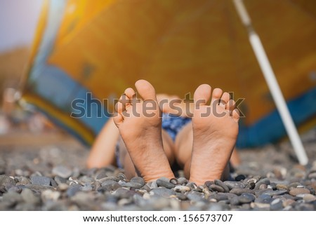 Children's feet  on pebbles. picnic on the beach - stock photo