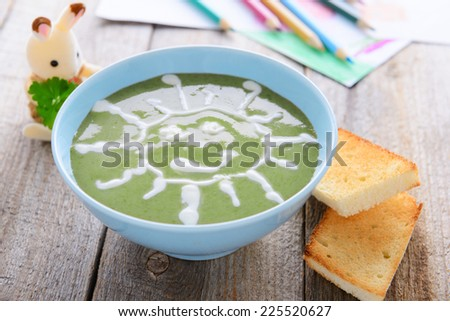Children`s food - spinach cream soup - stock photo