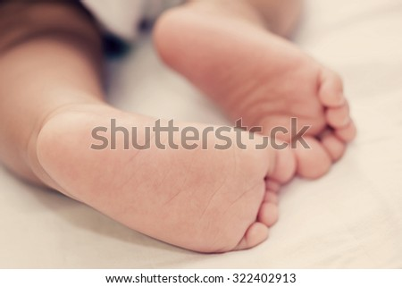 Children's foot on a white bedspread Close-up ,vintage style. - stock photo