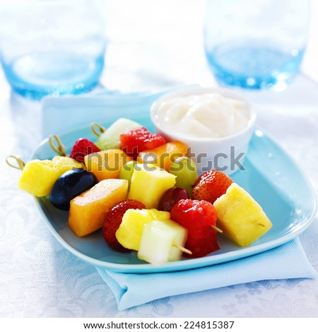 children's fruit kabob with vanilla yogurt dip on blue plate - stock photo