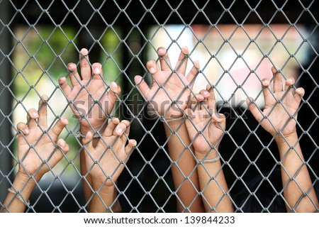 children's hand in jail. - stock photo