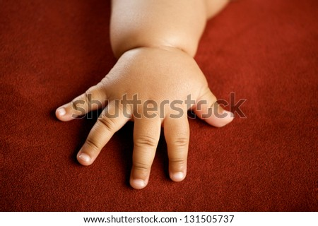 Children's hand isolated on red background - stock photo
