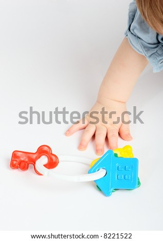 Children's hand tries to get a toy - stock photo