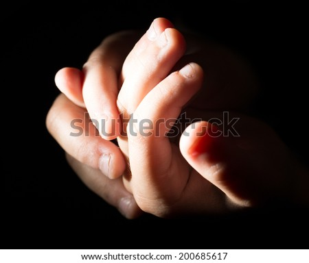 children's hands on a black background - stock photo