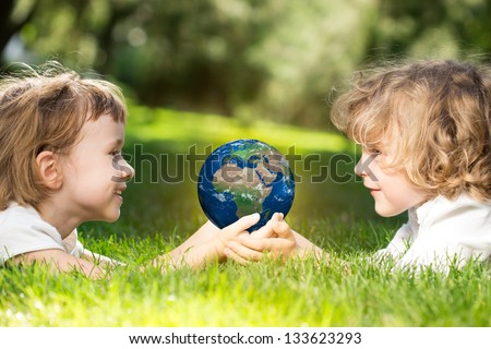 Children`s holding world in hands against green spring background. Earth day concept. Elements of this image furnished by NASA - stock photo