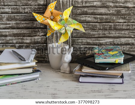 Children's home workspace with books, notebooks, notepads, tablet and handmade paper pinwheels and easter ceramic bunny. - stock photo
