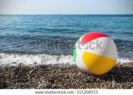 children's inflatable ball on the beach against the sea - stock photo