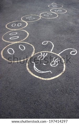 children's street game in a form of caterpillar drawn on the asphalt - stock photo