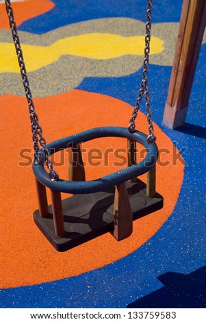 Children�s swing .Vertical view of a swing in a children�s playground  with vivid colors on the floor - stock photo