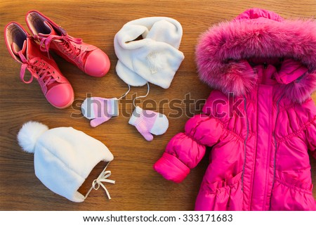 Children's winter clothes: warm pink jacket, hat, scarf, mittens, boots - stock photo