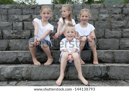 children seated outdoors on stairs - stock photo