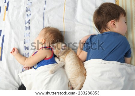 Children - sister and brother - and pet sleeping together - stock photo