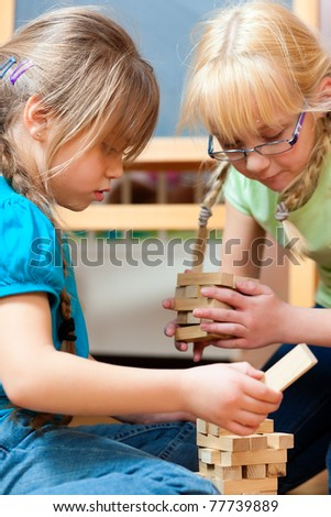 Children - sisters - playing at home with bricks - stock photo