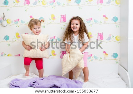 children sisters playing on the bed indoors - stock photo