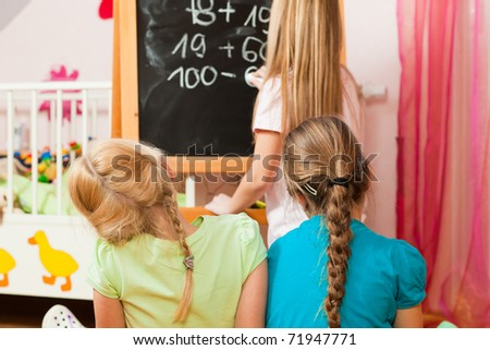 Children � sisters - playing school in their room - stock photo