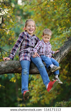 children sit on a high tree. Sunny summer day - stock photo