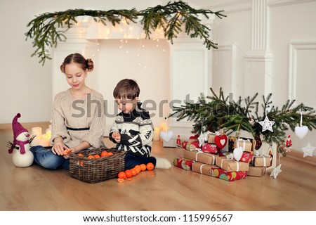 Children sit on the floor. Christmas and many decorations. - stock photo