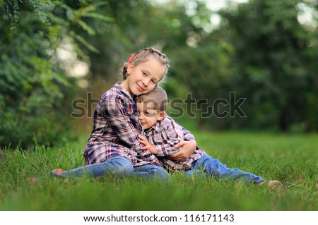 children sitting in green grass. Sunny summer day - stock photo