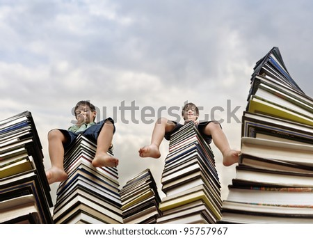 Children sitting on books - stock photo