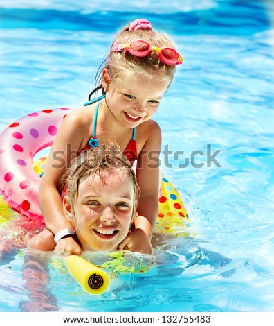 Children sitting on inflatable ring in swimming pool. - stock photo