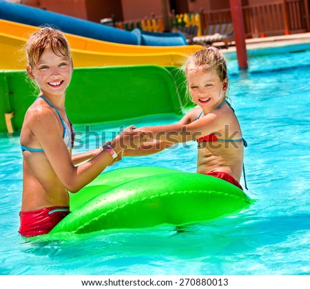 Children sitting on inflatable ring in swimming pool. Kids holding hands - stock photo