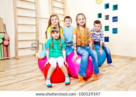 Children sitting on large gymnastic balls - stock photo
