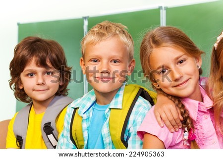 Children stand close to each other near blackboard - stock photo