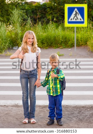 Children stand near a pedestrian crossing and showing thumbs up - stock photo