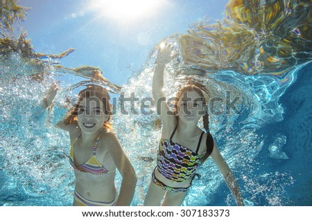 Children swim in pool underwater, happy active girls have fun in water, kids sport on family vacation  - stock photo