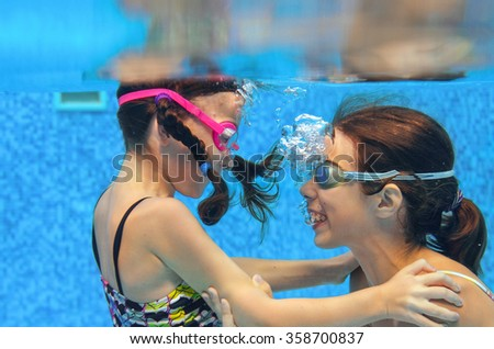 Children swim in pool underwater, happy active girls in goggles have fun in water, kids sport on family vacation  - stock photo