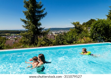 children swimming in the swimming pool in the garden - stock photo