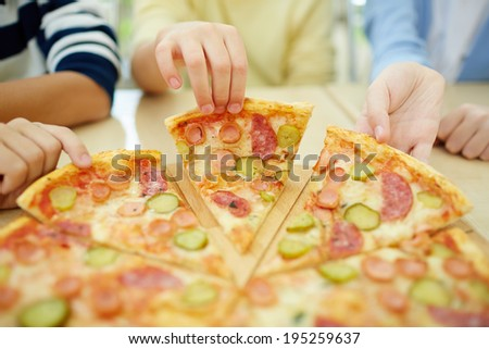 Children taking pieces of pizza  - stock photo